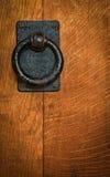 Oude zwarte cirkelkloppers op eiken deur Stock Afbeeldingen