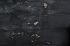 Oude, zwarte geschilderde concrete muur met barsten en spaanders in pleister stock foto's