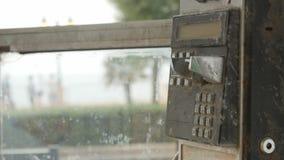 Oude zwarte roestige telefoon in telefooncelmuntstuk stock footage