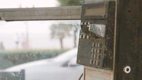 Oude zwarte roestige telefoon in telefooncelmuntstuk stock videobeelden