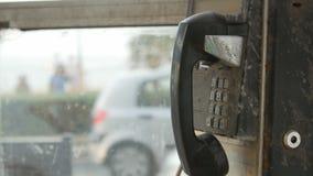 Oude zwarte roestige telefoon in telefooncelmuntstuk stock video