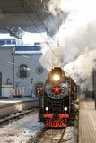 Oude zwarte stoomlocomotief in Rusland in de winter op de achtergrond van het station van Moskou Stock Afbeeldingen