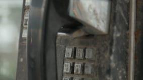 Oude zwarte telefoon in telefooncelmuntstuk stock footage