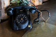 Oude zwarte uitstekende telefoon op een lijst, Retro telecommunicatie in vroeger tijden stock foto's