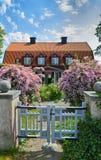 Oude Zweedse houten plattelandshuisje en bloemen Stock Afbeeldingen