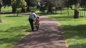 Ouder die een kind onderwijzen aan hoe te om fiets zonder stabilisatoren in het park te berijden stock videobeelden