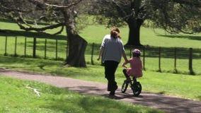 Ouder die een kind onderwijzen aan hoe te om fiets zonder stabilisatoren in het park te berijden stock video