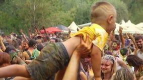 Ouder die weinig jongen in lucht bij festival, positieve mensen spinnen stock video