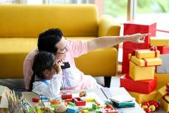 Ouder en weinig kind die pret hebben die onderwijsspeelgoed, Fami spelen stock foto's