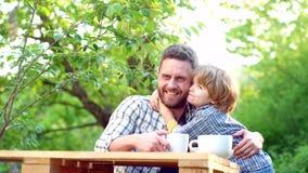 Ouder met baby De de lentetijd? nam bladeren, natuurlijke achtergrond toe De zomerrantsoen Leuk kind die ontbijt thuis in de tuin stock video