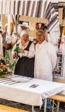 Ouder paar dat traditionele maaltijd en douane op een Samobor-viering van de stedendag voorstelt royalty-vrije stock foto's