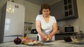 Ouder vrouw het kneden deeg op de lijst stock videobeelden