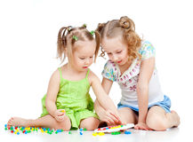 Ouder zuster opleidend kind om mozaïekstuk speelgoed uit te voeren Stock Foto