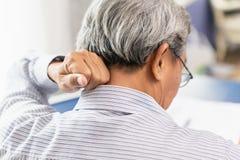 Oudere achterhalspijn die hand gebruiken aan massage royalty-vrije stock afbeeldingen