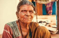 Oudere Aziatische vrouw die met vriendelijk, gerimpeld gezicht in Indisch dorp leven stock foto's