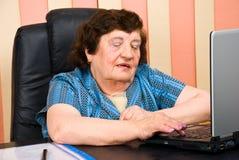 Oudere bedrijfsvrouw in bureau dat laptop met behulp van Stock Foto's