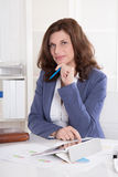 Oudere bedrijfsvrouwenzitting in haar bureau. Royalty-vrije Stock Afbeelding