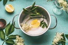 Oudere bloemen in het koken van pot met suiker en citroen op blauwe lijstachtergrond, hoogste mening royalty-vrije stock afbeeldingen