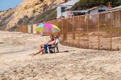 Oudere boomers van de paarbaby zitten op strand onder paraplu dichtbij een omheining van de kettingsverbinding met dilapidated hu stock afbeelding