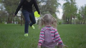 Oudere broer en kleine zuster die in mooi groen park in werking wordt gesteld De kleine meisjesdaling beneden en de jongen helpen stock videobeelden