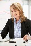 Oudere carrièrevrouw aan het werk in bureau Stock Foto