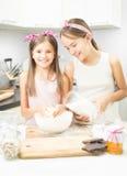 Oudere en jonge zuster die deeg op keuken in witte kom maken royalty-vrije stock afbeeldingen