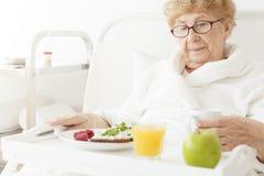 Oudere het eten maaltijd bij het ziekenhuis royalty-vrije stock foto