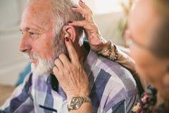 Oudere man en vrouw of gepensioneerden met een hoorzittingsprobleem stock afbeeldingen
