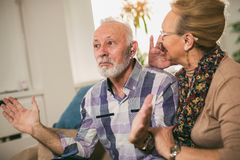 Oudere man en vrouw of gepensioneerden met een hoorzittingsprobleem royalty-vrije stock afbeelding
