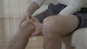 Oudere mens die aan reumatische pijnziekte lijden die zijn pijnlijke en pijnlijke knie wrijven die doen massagetherapie - stock footage