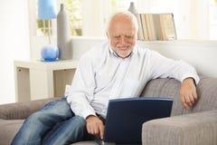 Oudere mens die bij het computerscherm thuis glimlacht Royalty-vrije Stock Afbeeldingen