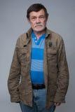 Oudere mens die zich met gekruiste wapens bevinden Royalty-vrije Stock Afbeeldingen