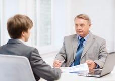 Oudere mens en jonge mens die vergadering in bureau hebben Royalty-vrije Stock Afbeeldingen