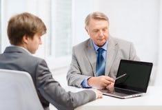Oudere mens en jonge mens met laptop computer Stock Afbeeldingen