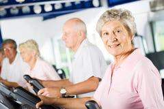 Oudere mensen die in de gymnastiek uitoefenen Stock Foto's