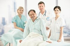 Oudere patiënt op bed met het ziekenhuisbemanning Royalty-vrije Stock Foto's
