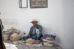 Oudere straatventer die met de hand gemaakte herinneringen verkopen Stock Foto's
