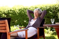 Oudere vrouw die in binnenplaatstuin rusten Stock Foto