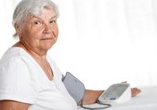 Oudere vrouw die bloeddruk met automatische manometer meten Stock Foto