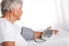 Oudere vrouw die bloeddruk met automatische manometer meten bij Stock Afbeelding