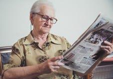 Oudere vrouw die en krant ontspannen lezen stock foto's