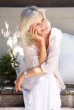 Oudere vrouw die en op portiek buiten glimlachen zitten royalty-vrije stock foto