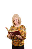 Oudere vrouw die in het boek van het Adres controleert stock foto
