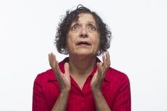 Oudere vrouw die omhoog in horizontaal ongeloof kijken, royalty-vrije stock afbeelding