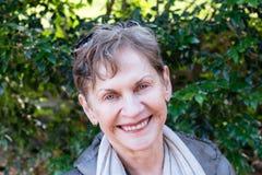 Oudere vrouw die in openlucht glimlachen stock afbeelding