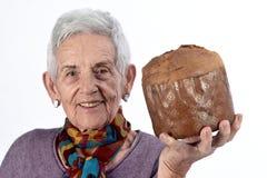 Oudere vrouw die panettone op witte achtergrond eten royalty-vrije stock foto's