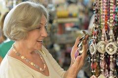 Oudere vrouw in een herinneringswinkel Stock Afbeelding
