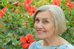 Oudere vrouw met bloemen royalty-vrije stock fotografie