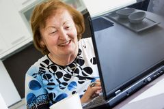 Oudere vrouw met een computer Stock Afbeeldingen