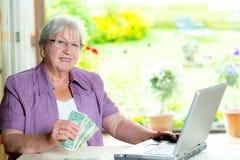 Oudere vrouw met geld en computer Royalty-vrije Stock Foto